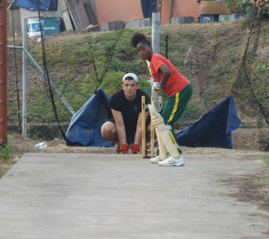 Volunteer coach working with a girls cricket team in the Caribbean