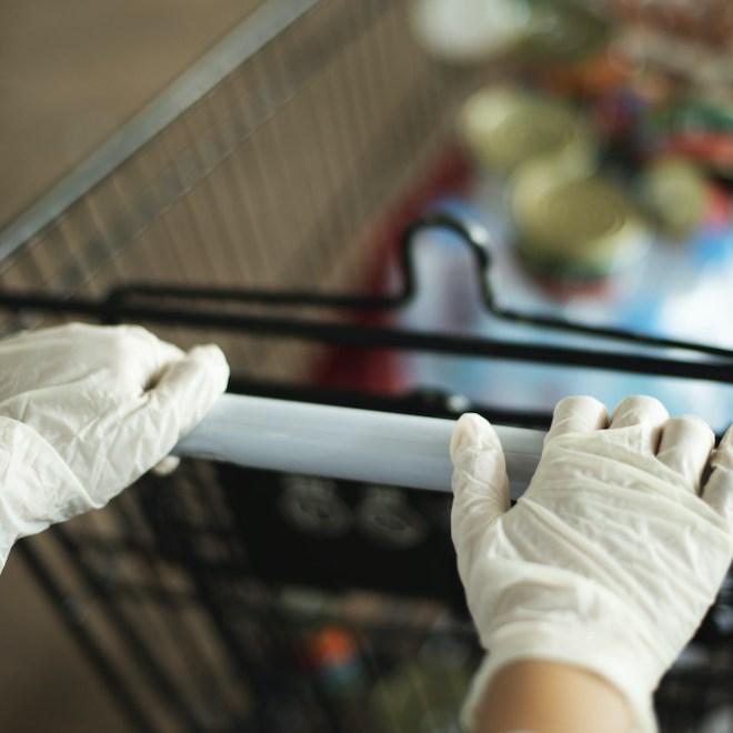 Femme qui porte des gants au supermarché