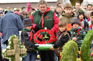 Scouter Jamie Mannen helps Cohen Herman and Mira Knechtel of the First Coldstream Scouts place a homemade wreath at the Coldstream cenotaph during the Remembrance Day Ceremony