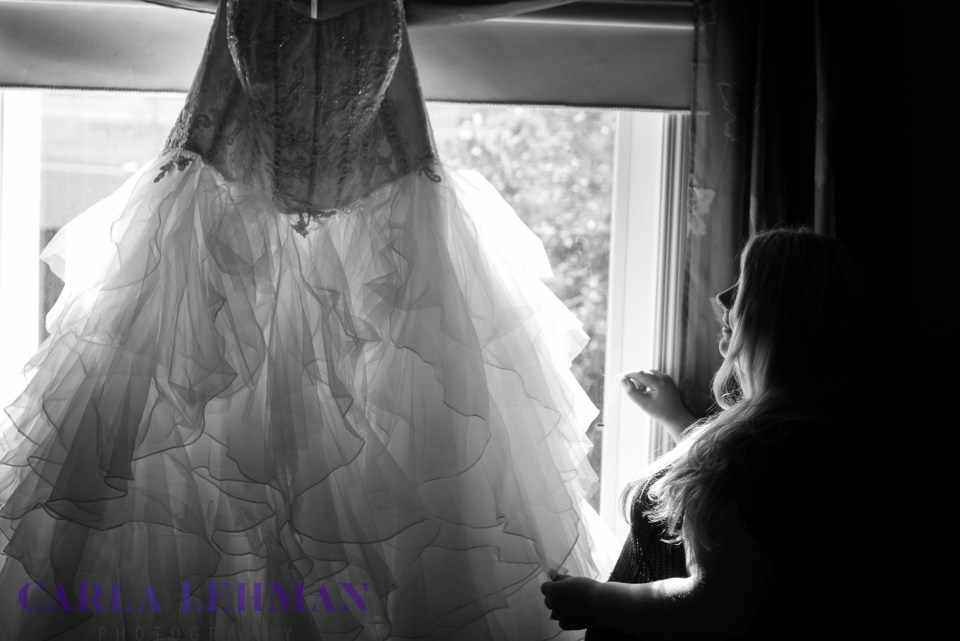 The beautiful bride gazes on her gown, shortly before her Camrose Alberta wedding