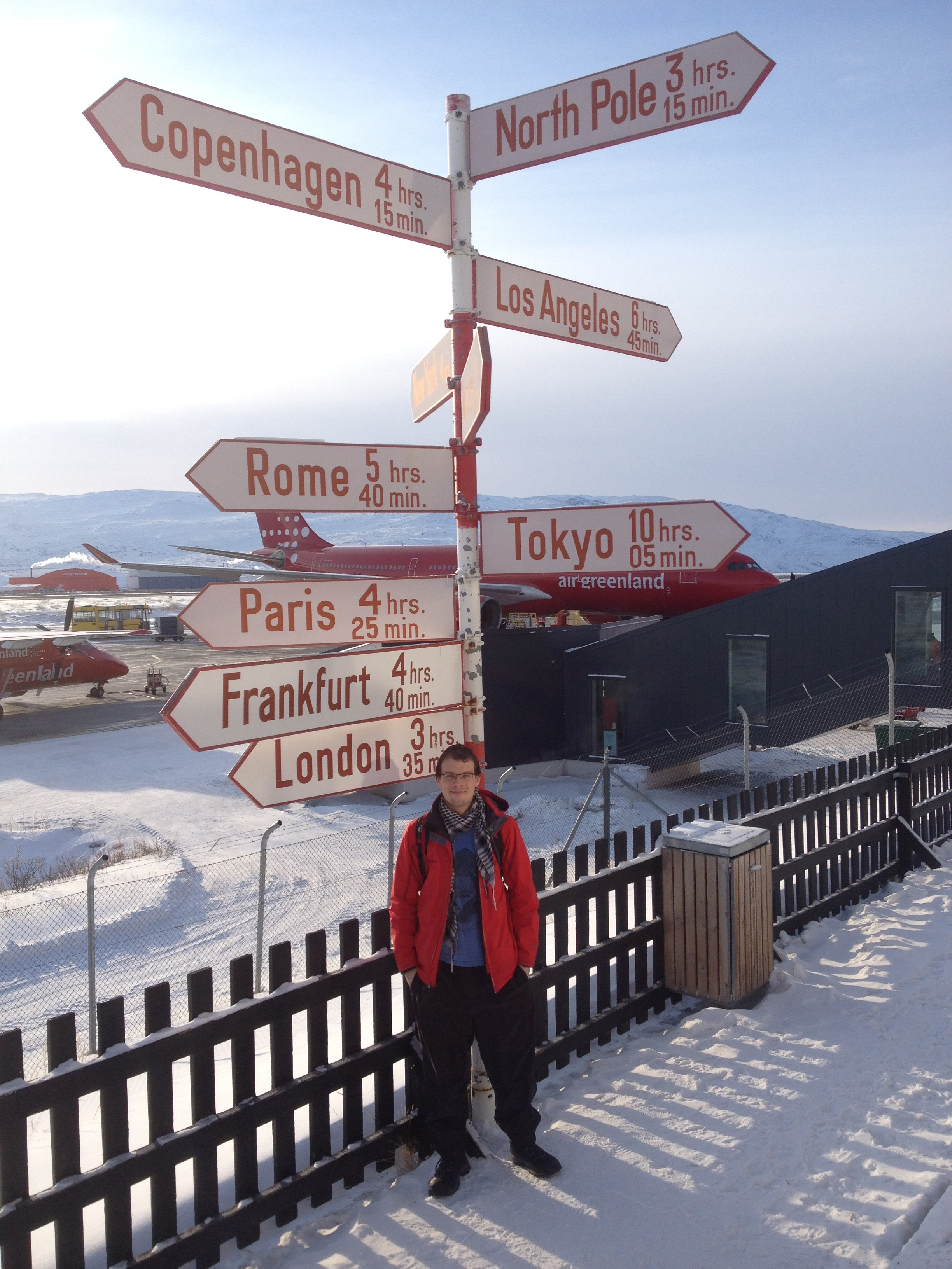 Carleton M.Sc. student Keegan Smith standing under the Kangerlussuaq airport signpost, north of the Arctic Circle.