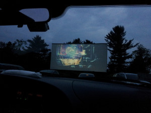 Saco Drive-In screen at twilight, showing a movie