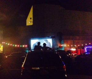 Cars and a small drive-in screen at night