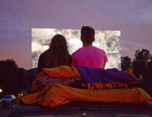 A couple with blankets watching the drive-in screen