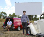 Man and teenager in front of a drive-in screen