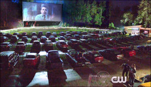 Full drive-in theater lot watching a movie, with CW logo