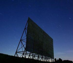 Drive-in screen silhouette against starry sky