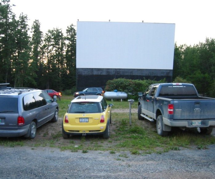 Cars parked in front of a drive-in screen