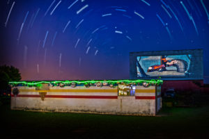 Blue Moonlight Drive-In concession stand and screen at night with starts circling above