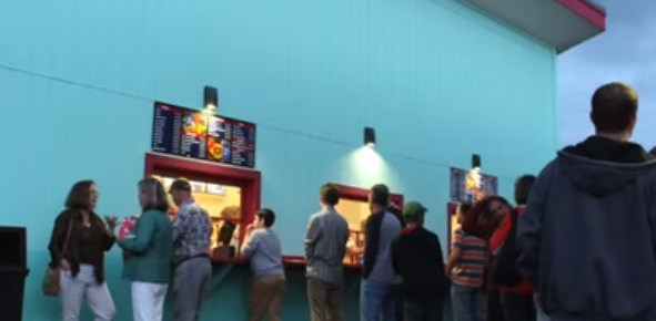 Outdoor concession stand window with customers lined up