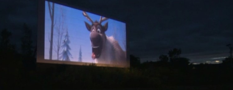 Drive-in screen showing a movie at night