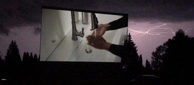 Drive-in screen showing a movie at night with lightning in the background