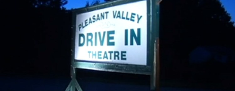Wooden sign for the Pleasant Valley Drive-In illuminated at night
