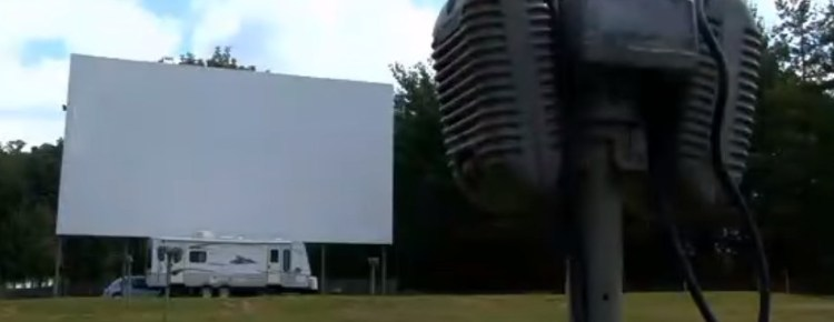 Drive-in screen with speakers in the foreground