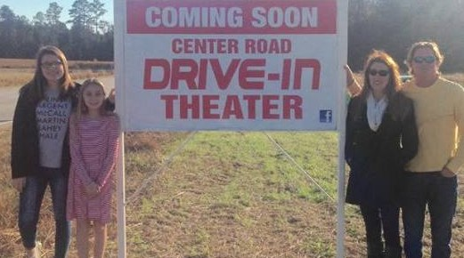 Four people standing next to a sign that reads Coming Soon - Center Road Drive-In