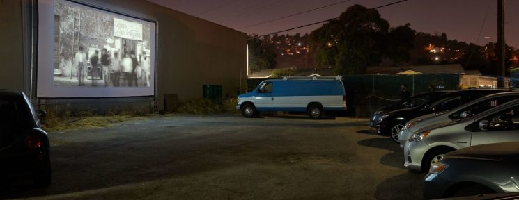 A small line of cars watching a movie on a screen against a wall