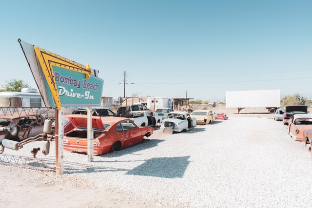 """Bombay Beach """"Drive-In,"""" an art installation of junk cars facing a white tractor-trailer """"screen"""""""