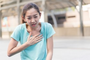 woman experiencing acid reflux while running