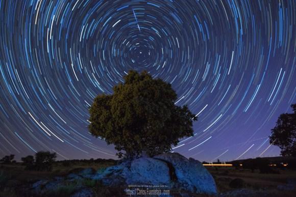 Foto nocturna con aplilamiento de imagenes mostrando el movimiento de las estrellas y un tren, centrado sobre una encina.