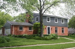 Dark grey siding, dark grey straight edged shakes, carriage style over lay garage doors, red brick