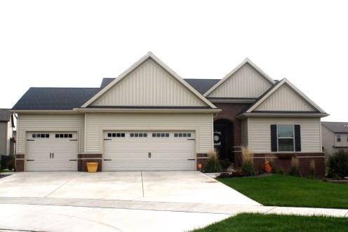 Black roof, tan carriage style garage door, Mastic wicker tan vertical siding, Mastic wicker tan siding in Normal IL