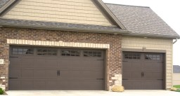 brown-carriage-style-garage-door-in-bloomginton-il-with-gridded-window-panes-and-keystone-casings-in-wexford-subdivision
