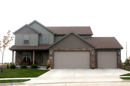 two story ranch with green siding, brown shakes, tan garage door, brown brick