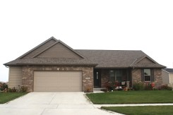rand style home with brown brick front, tan garage door, tan siding, dark brown shakes in gables