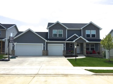 TWO STORY HOUSE WITH dark grey siding and grey shakes with white trim and black roof white garage door and stone accents