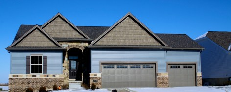 one story blue house with brick. stone ledger around house. brown garage doors and faux cedar shakes