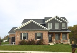 2 story ranch house with dark grey vertical siding, dark grey metal porch roof, dark grey roof, red brick and stone accents