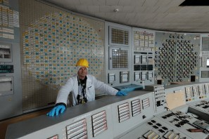 A visitor stands behind A Desk (reactor control engineer's position) in the Unit 2 control room, ChNPP.