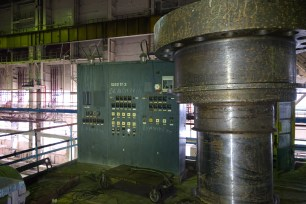 Part of a turbine shaft belonging to TG-3 stands next to a decommissioned control station.