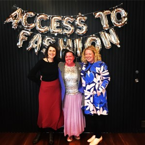 three women looking happy, standing in front of a silver balloon letting that reads Access to Fashion