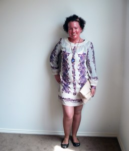 Woman with red face and short dark curly hair, standing against a wall smiling. She's wearing a short white and purple long sleeved dress, and is holding a pink clutch bag. Her legs are bare.