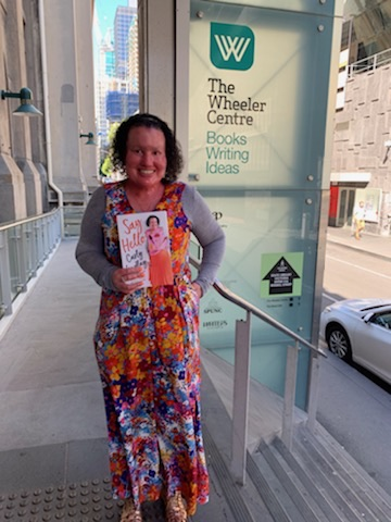 Woman with red face and shirt dark curly hair, holding a book, standing outside a building, behind her is a signsahijt The Wheeler Centre