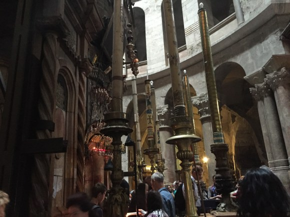 Tomb of Christ stone entrance flanked by rows of huge candles.  The Church of the Holy Sepulchre