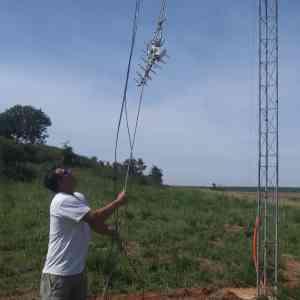 Travis Ridgeway hoists up a rope carrying a small UHF antenna.
