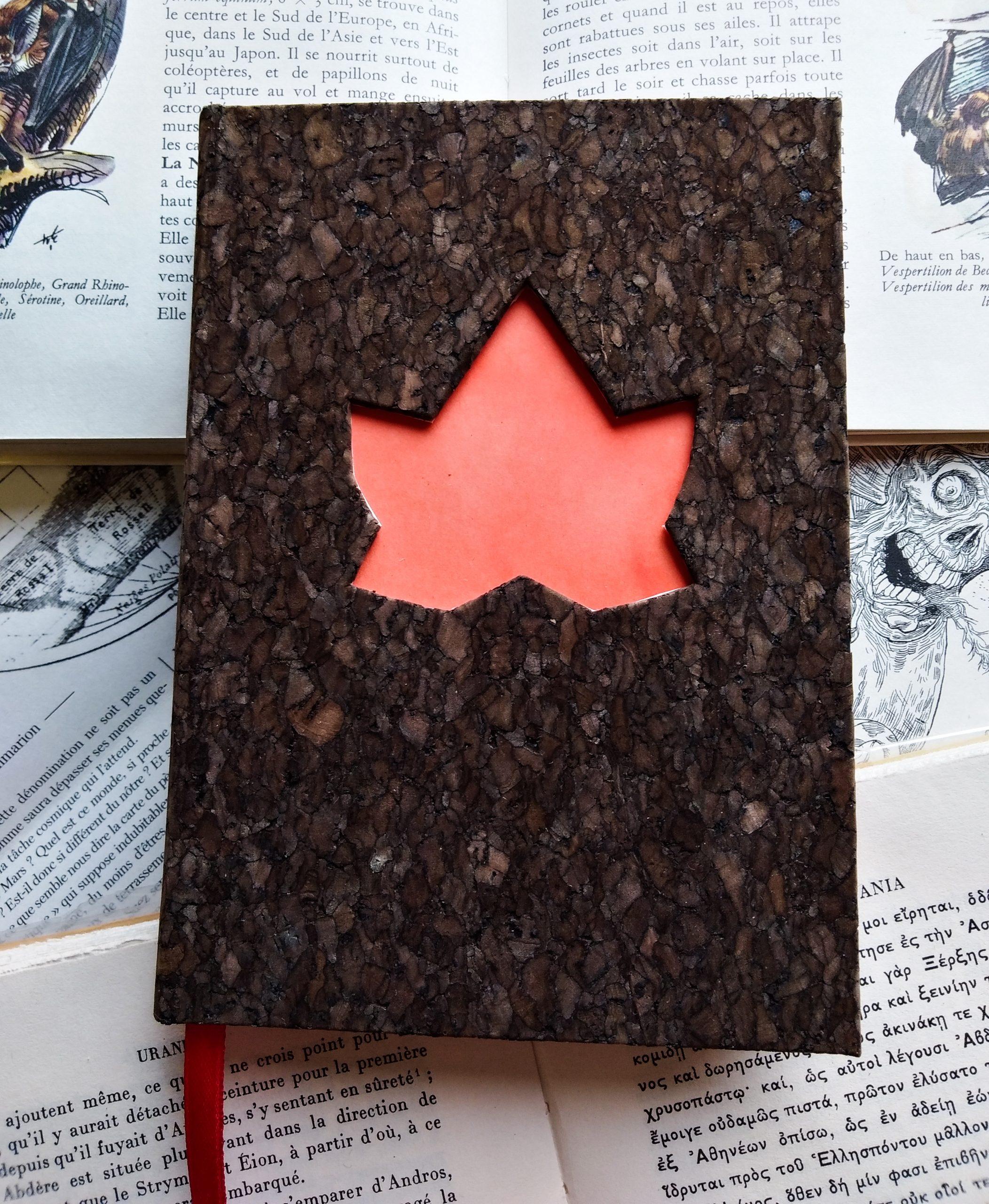 Carnet couvert en liège sombre, avec une ouverture en forme de feuille de lierre dans la couverture.