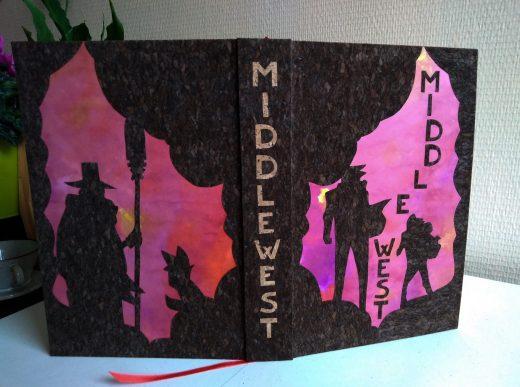 Couverture de la reliure de l'intégrale de Middlewest, sur laquelle les personnages principaux apparaissent en ombres découpées dans le liège, sur fond d'un papier à l'encre violette.