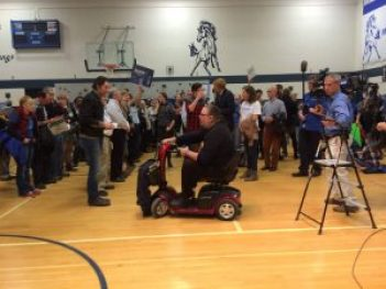 Des Moines, Iowa, caucus goers stand to be counted. Action of great interest to media. Photo courtesy of Robin Fortney