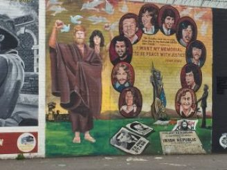 """The republican prisoners commemorated in this mural sought prisoner of war status. Rather than wear prison garb, they opted for blankets; their action became known as """"the blanket protest."""" The prisoners also initiated a hunger strike. Some died before the protest ended."""