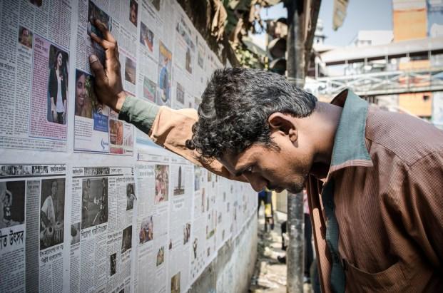 Die Leute informieren sich durch Zeitungen, die an Mauern aufgehängt werden, über das aktuelle Geschehen.