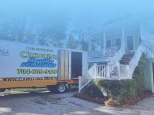 Carolina Moving Solutions truck pulled up to a house, prepared to load up boxes.