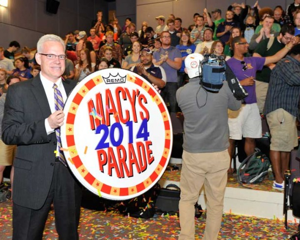 David Starnes, director of Western Carolina University's Pride of the Mountains Marching Band, displays a commemorative drum head while students celebrate an invitation to participate in the 2014 Macy's Thanksgiving Day Parade. Photo by Mark Haskett and courtesy of Western Carolina University.