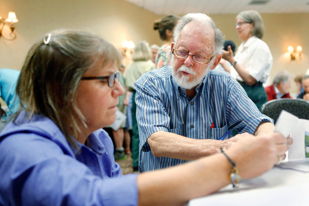 Sheryl Bryan, a fish and wildlife biologist with the National Forests of North Carolina, left, speaks with Sierra Club volunteer Bill Thomas, right, at a U.S. Forest Service meeting on the Pisgah and Nantahala national forests in July. Thomas expressed the desire to keep the national forests in a natural state that existed before the area was settled. Matt Rose/Carolina Public Press