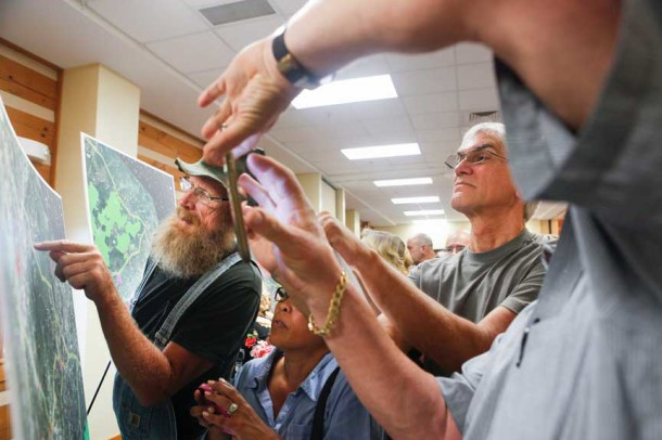 Residents snapped photos of some of the maps presented by Duke Energy during an informational meeting held on Tuesday about the company's plans to construct a 45-mile high-voltage power line through Henderson and Polk Counties. Matt Rose/Carolina Public Press