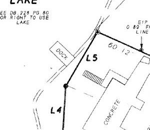 Larry Hultquist's plat of his property shows his boundary with the town's lake bed property running between a set of steps and a dock. The steps and a related retaining wall are clearly on his property.