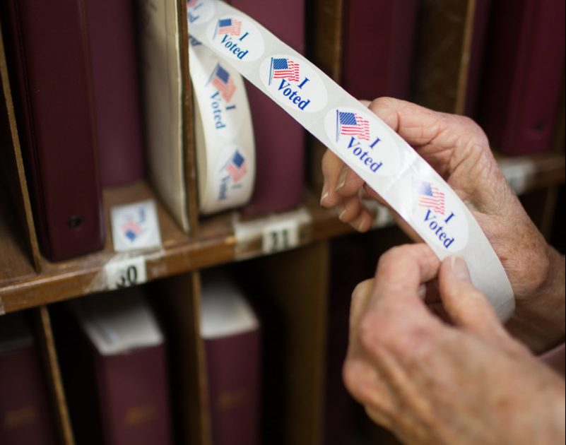 """A poll worker pulls out a """"I voted"""" sticker at the First Baptist Church of Black Mountain polling place in Buncombe County on March 3, 2020. Colby Rabon / Carolina Public Press"""