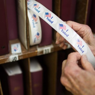 "A poll worker pulls out a ""I voted"" sticker at the First Baptist Church of Black Mountain polling place in Buncombe County on March 3, 2020. Colby Rabon / Carolina Public Press"